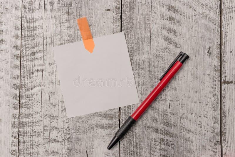 Un papier de note simple plus le stylo sticked à la table en bois Page blanche et stationnaire attachés avec le bureau texturisé  photos stock
