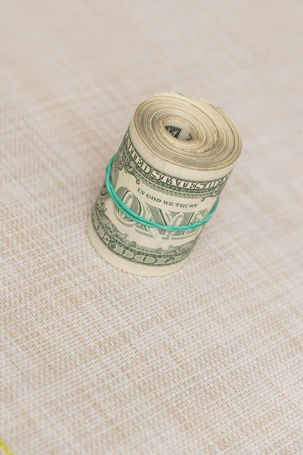 Un paquet d'argent tordu dans un paquet et attaché avec une bande élastique verte images libres de droits
