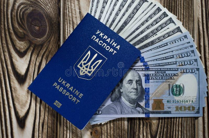 Un paquet de billets de banque de 100 dollars dans un passeport étranger bleu biométrique d'un citoyen de l'Ukraine photographie stock