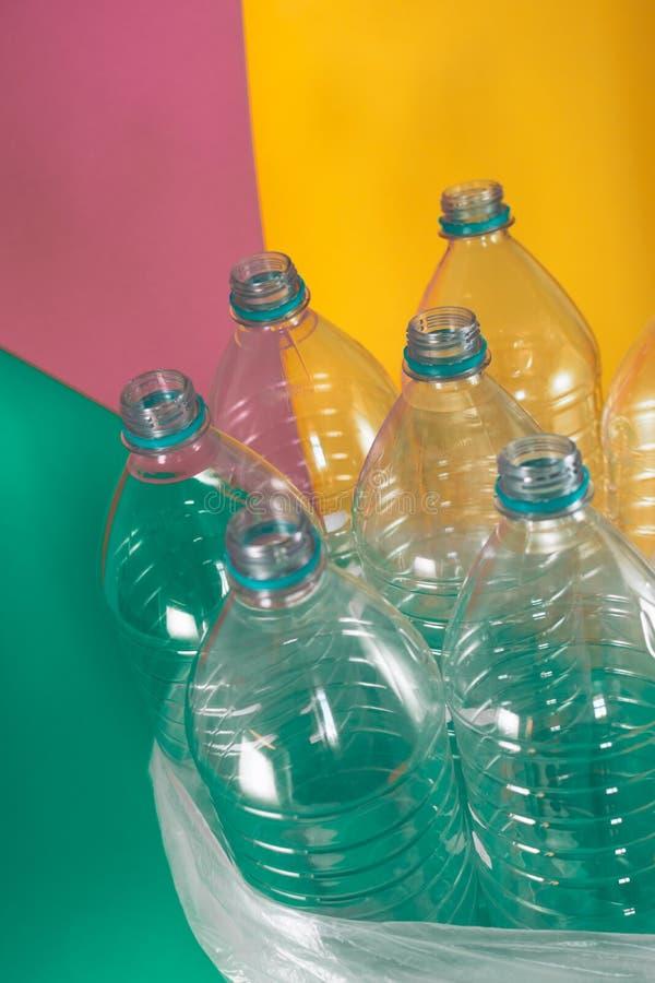 Un paquete de 7 vacíos y de botellas de agua plásticas reciclables, sin los casquillos, sello azul, en una bolsa de plástico, en  imagenes de archivo