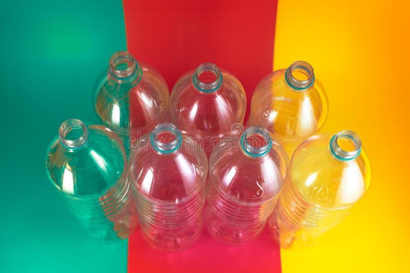 Un paquete de 7 vacíos y de botellas de agua plásticas reciclables, sin los casquillos, sello azul, en un verde de mar vibrante c imagenes de archivo