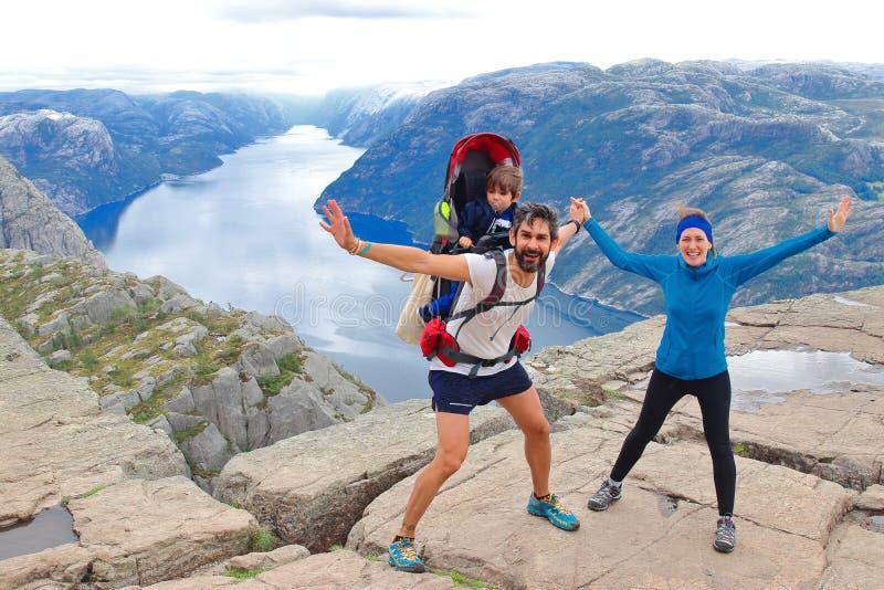 Un par alegre y su niño en la cumbre de la roca Preikestolen, Noruega del púlpito fotos de archivo