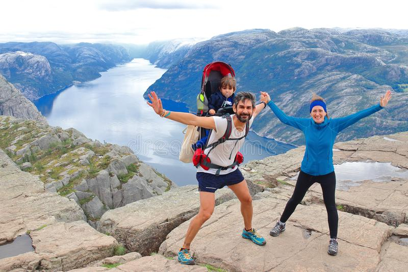 Un par alegre y su niño en la cumbre de la roca Preikestolen, Noruega del púlpito foto de archivo