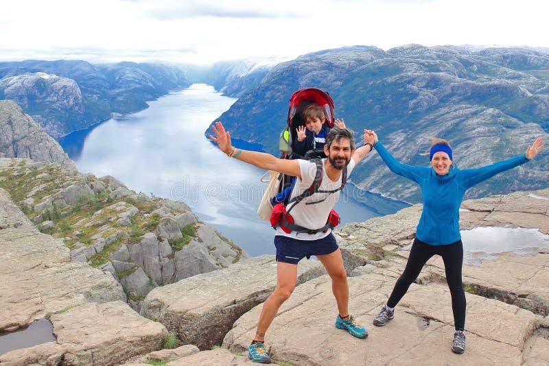 Un par alegre y su niño en la cumbre de la roca Preikestolen, Noruega del púlpito imagenes de archivo