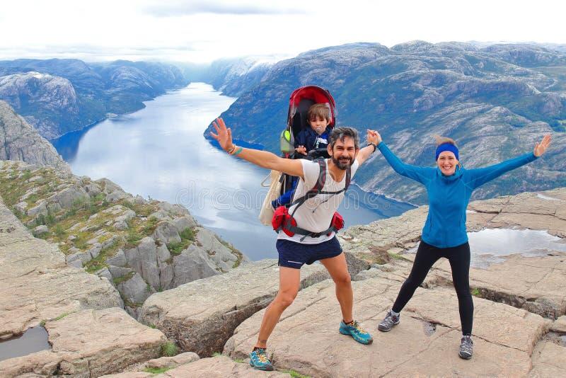 Un par alegre y su niño en la cumbre de la roca Preikestolen, Noruega del púlpito imagen de archivo libre de regalías