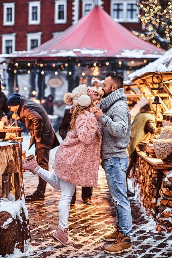 Un par atractivo en amor, divirtiéndose junto en una feria de la Navidad imagen de archivo libre de regalías