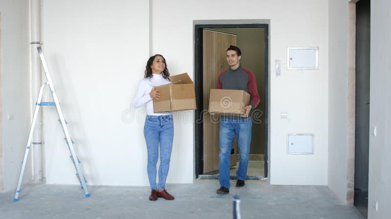 Un par atractivo joven que se traslada a un nuevo hogar Un par se est? colocando en el umbral que sostiene las cajas en sus manos fotos de archivo