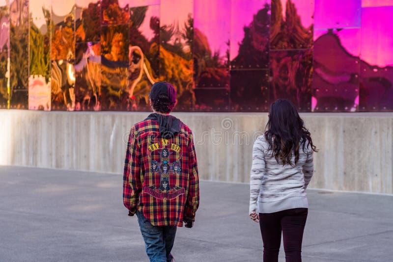 Un par camina por las paredes coloridas y vibrantes del museo del cultura Pop en Seattle foto de archivo libre de regalías