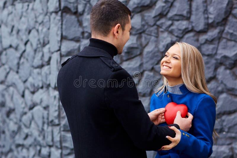 Un par cariñoso con un corazón en un fondo gris imágenes de archivo libres de regalías