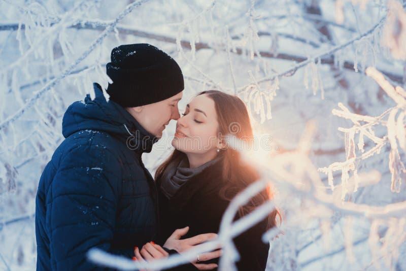 Un par cariñoso en un paseo del invierno Historia de amor de la nieve, magia del invierno Hombre y mujer en la calle escarchada E fotografía de archivo libre de regalías