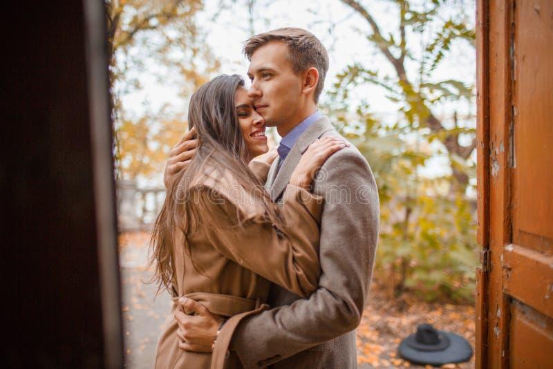 Un par cariñoso que abraza la colocación en la puerta afuera en un parque del otoño imagen de archivo libre de regalías