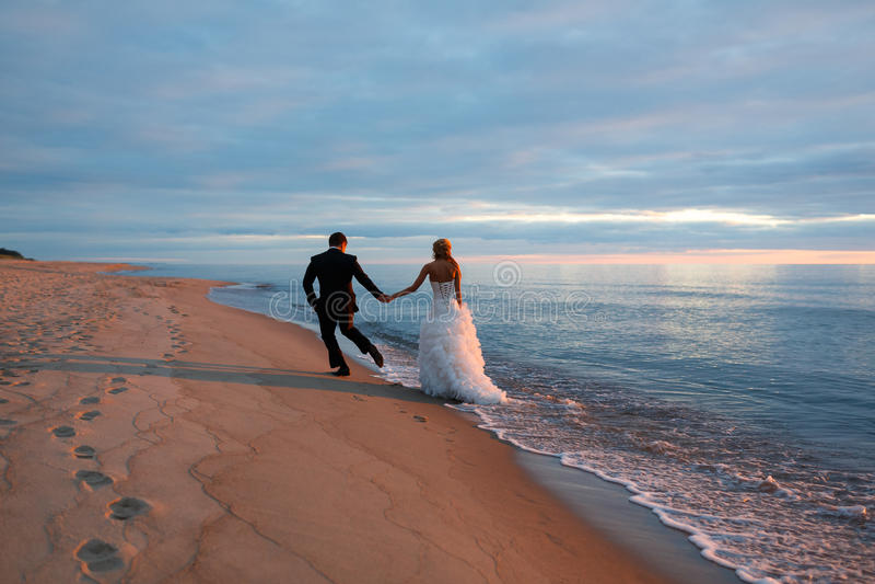 Un par cariñoso que camina por la costa de mar imagen de archivo