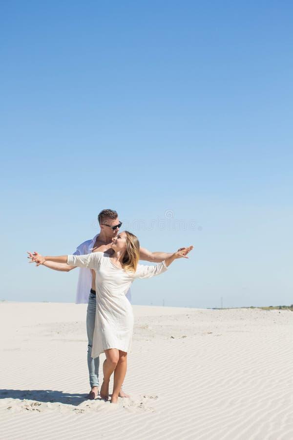 Un par cariñoso se está colocando con sus manos en el sol caliente foto de archivo libre de regalías