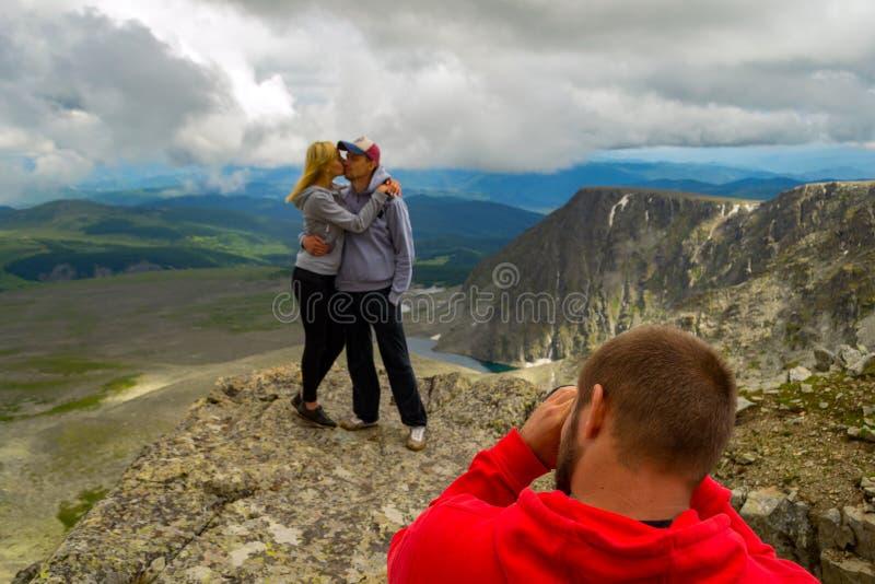 Un par cariñoso se está colocando en la montaña que se besa delante de fotografía de archivo