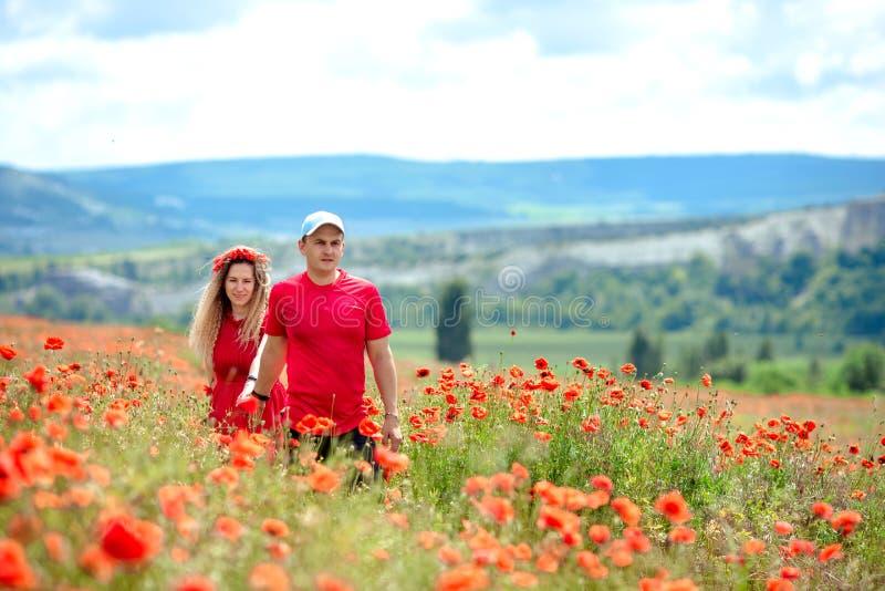 Un par cari?oso se est? divirtiendo en un campo con las flores de la amapola fotografía de archivo libre de regalías