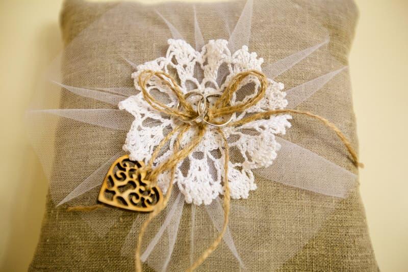 Un par de anillos de bodas en una almohada de la arpillera imagen de archivo libre de regalías