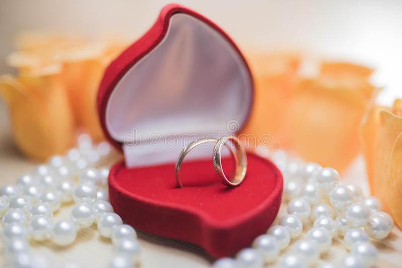 Un par de anillos de bodas en una caja de regalo roja fotos de archivo