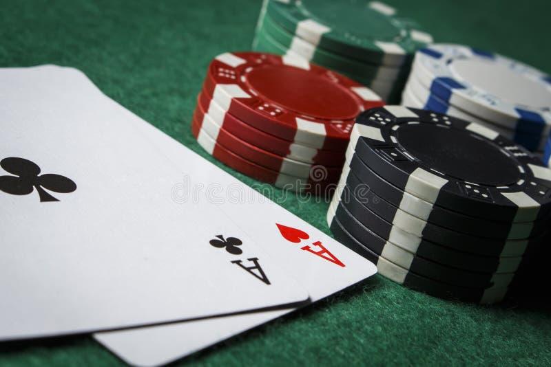 Un par de as con una pila de fichas de póker fotos de archivo libres de regalías