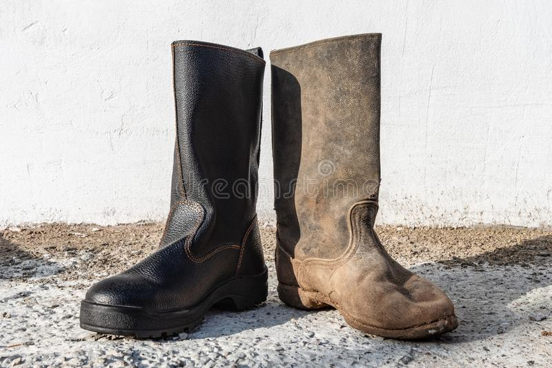 Un par de botas diferentes al aire libre Contraste zapatos viejos y nuevos, limpios y sucios fotos de archivo