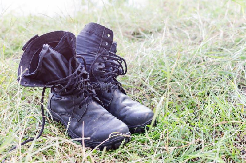 Un par de botas llevadas viejas en la hierba foto de archivo libre de regalías