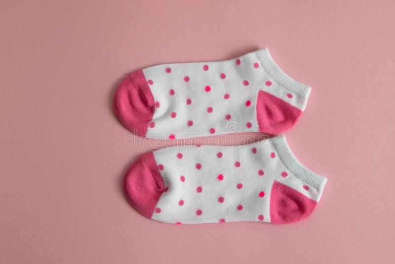 Un par de calcetines blancos para los niños con los calcetines rosados y los talones, con los puntos rosados, en un fondo rosado  fotos de archivo