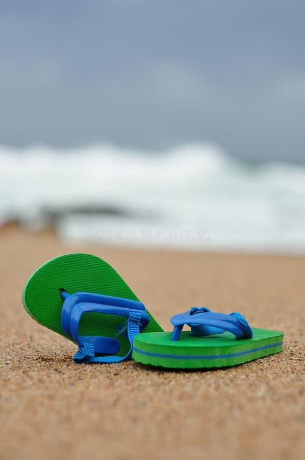 Un par de chancletas verdes y azules en la playa imagen de archivo libre de regalías