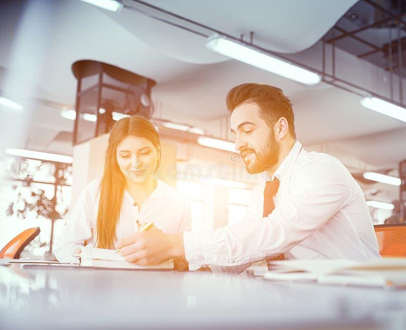 Un par de colegas en el escritorio en oficina soleada imagen de archivo