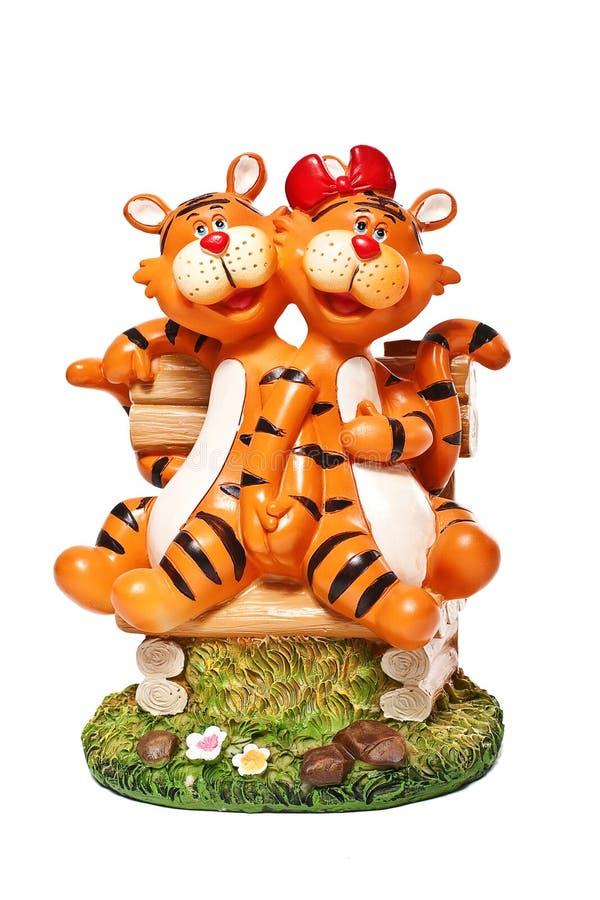 Un par de figuras divertidas tigres de la historieta del yeso que se sienta en un banco de madera foto de archivo libre de regalías