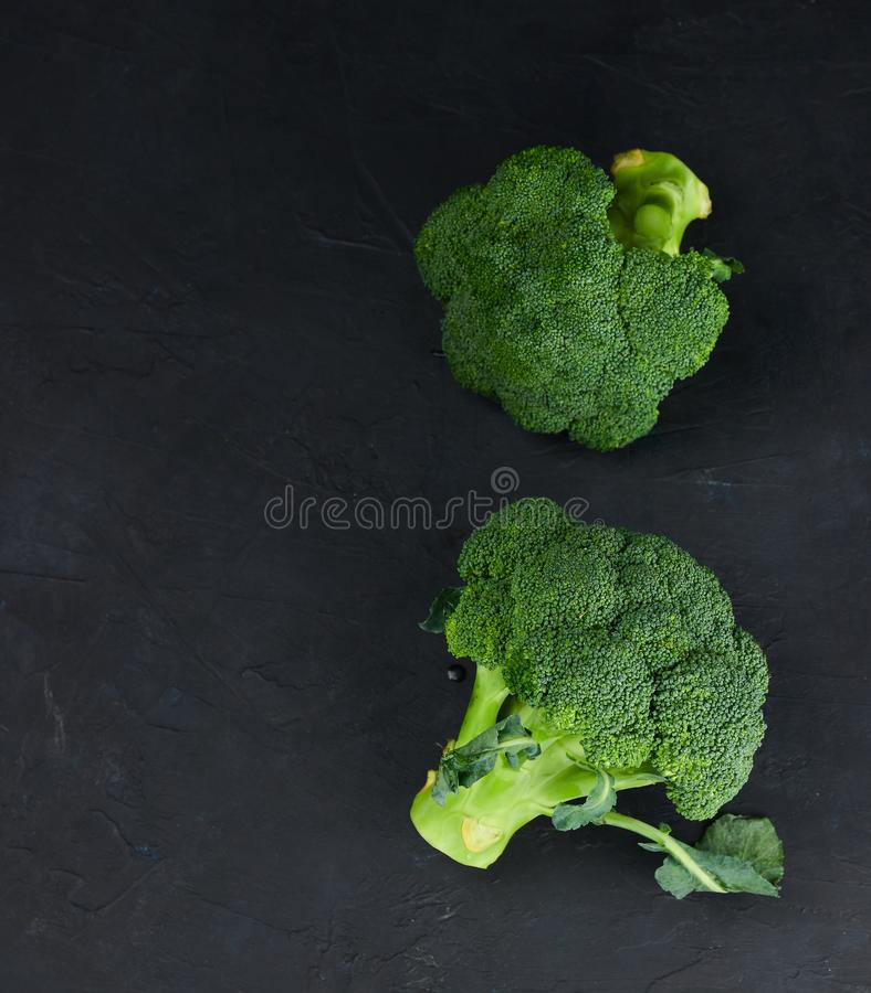 Un par de fresco, crudo, bróculi en un fondo negro La visión desde la tapa Alimento sano imagen de archivo libre de regalías