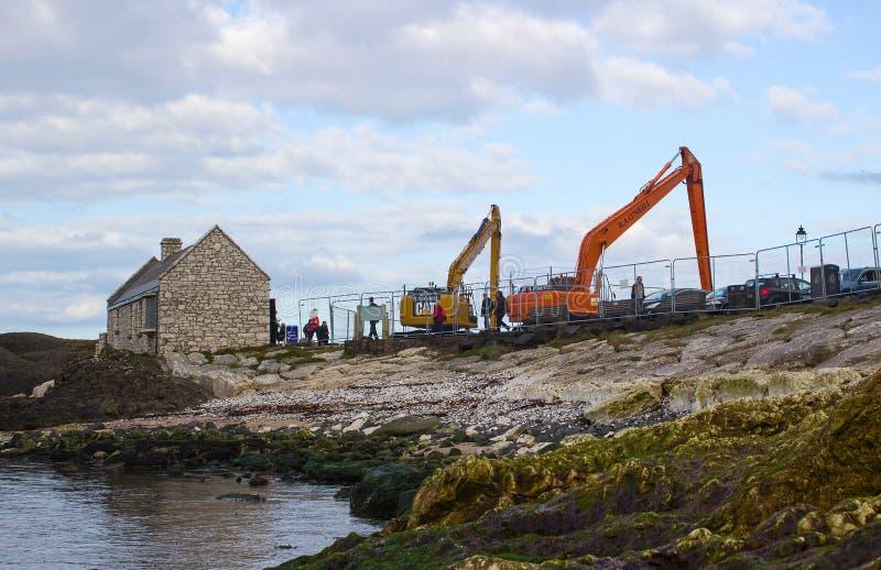 Un par de grúas listas para dragar el pequeño puerto en Ballintoy en la costa del norte de Antrim de Irlanda del Norte en un día  imágenes de archivo libres de regalías