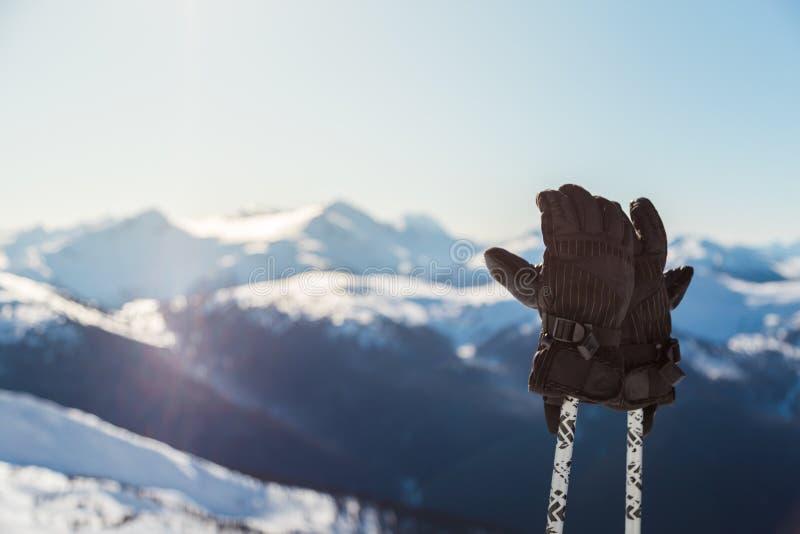 Un par de guantes del esquí en polos con los picos de montaña nevosos en el fondo en un día soleado fotos de archivo