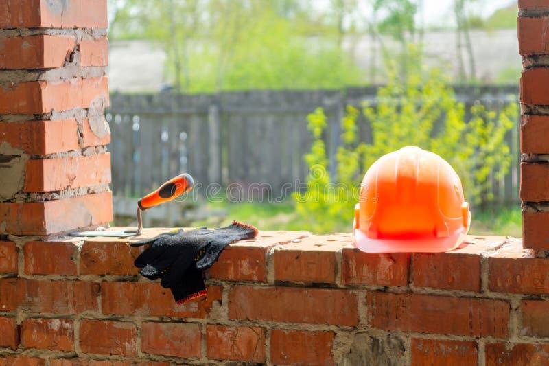 Un par de guantes y del casco de un albañil en la construcción imágenes de archivo libres de regalías