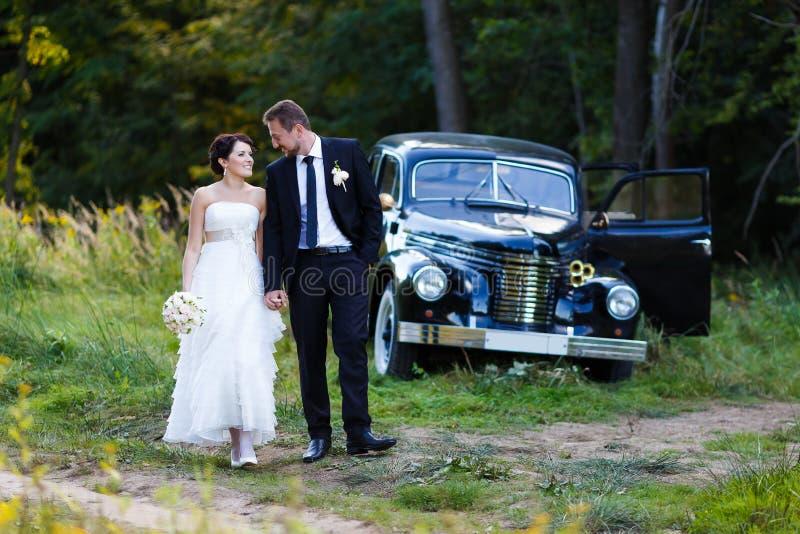 Un par de la boda con el coche viejo fotos de archivo