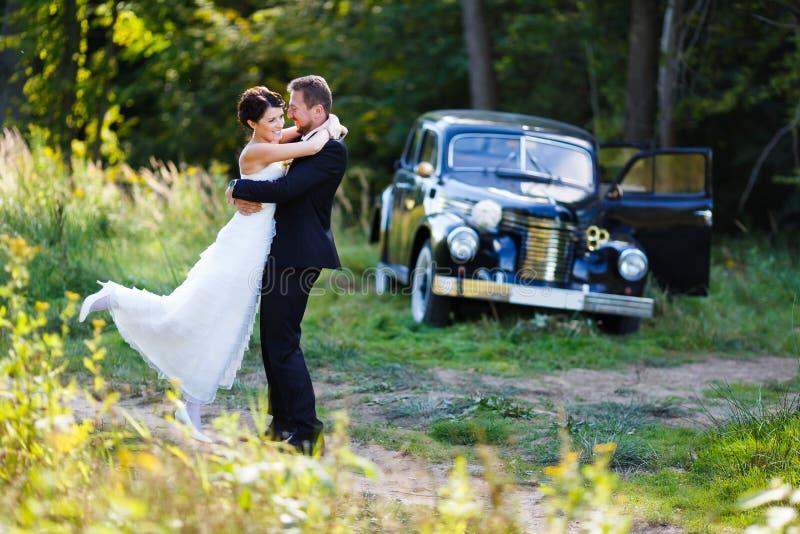 Un par de la boda con el coche viejo fotos de archivo libres de regalías