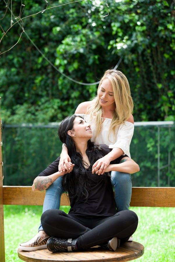 Un par de lesbiana orgullosa en al aire libre sentarse en una tabla de madera, mujer rubia está abrazando a una mujer morena, en  fotografía de archivo
