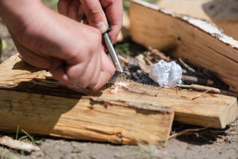 Un par de manos que hacen un fuego con pedernal y acero fotos de archivo libres de regalías