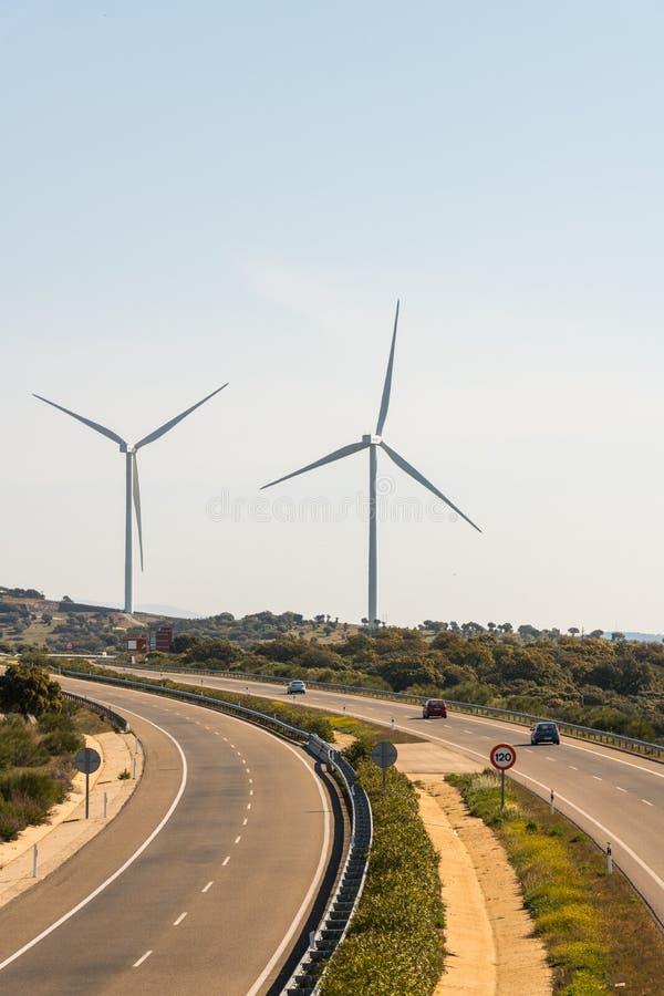 Un par de molinoes de viento en el parque eólico de Sierra del Merengue al lado de la carretera de Ruta de la Plata que pasa a tr fotos de archivo