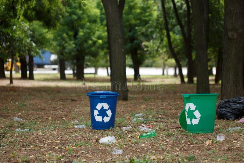 Un par de papeleras de reciclaje coloridas en un fondo natural borroso Envases para el reciclaje de la basura ecología imágenes de archivo libres de regalías
