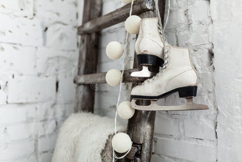 Un par de patines de los deportes del cuero blanco cuelga en un cordón en la pared Buen alcohol del Año Nuevo Fondo tranquilo her imágenes de archivo libres de regalías