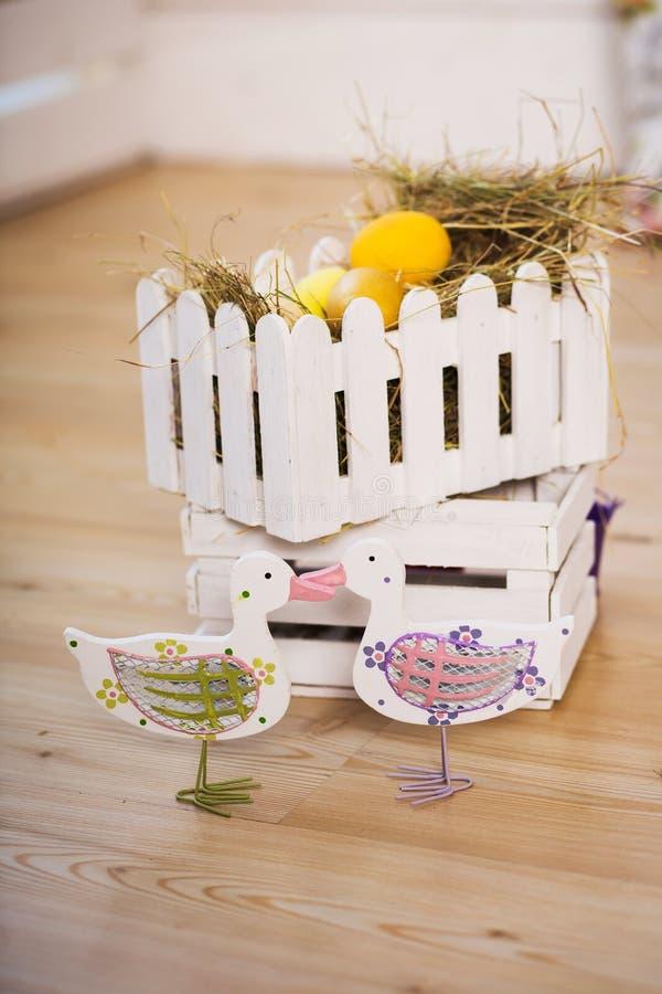 Un par de patos decorativos en el fondo de la jerarquía con los huevos de Pascua Fondo de Pascua foto de archivo
