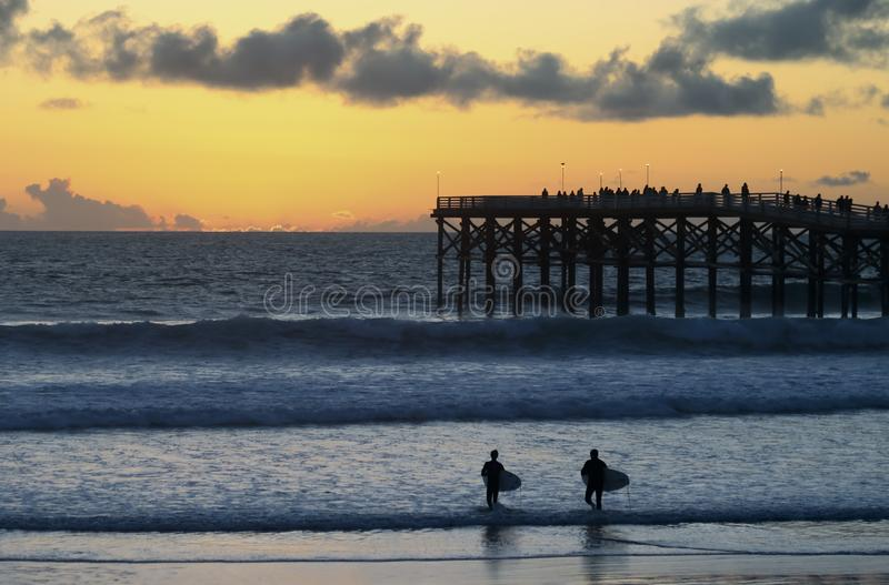 Un par de personas que practica surf de la puesta del sol en Crystal Pier, San Diego, CA imagenes de archivo