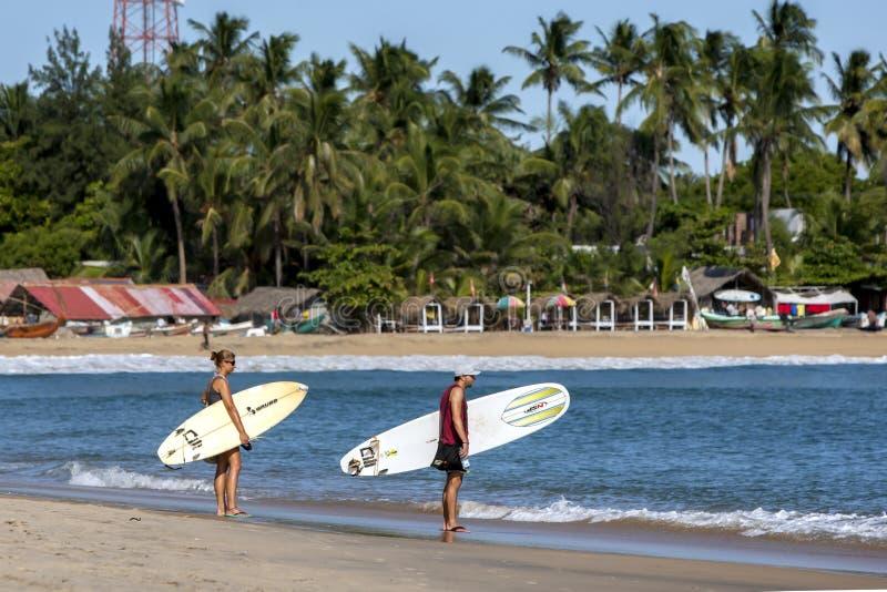 Un par de personas que practica surf mira hacia las ondas de la rotura del punto la bahía de Arugam en Sri Lanka imagen de archivo libre de regalías