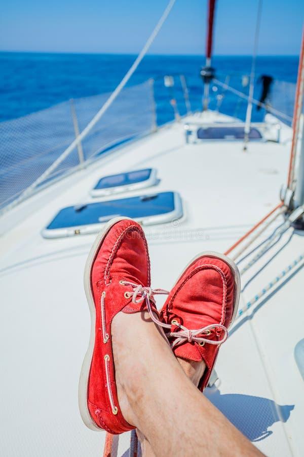 Un par de piernas del hombre en topsiders en la cubierta blanca del yate yachting fotos de archivo libres de regalías