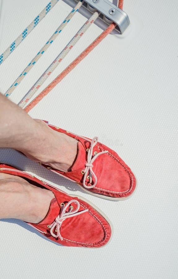 Un par de piernas del hombre en topsiders en la cubierta blanca del yate yachting imágenes de archivo libres de regalías