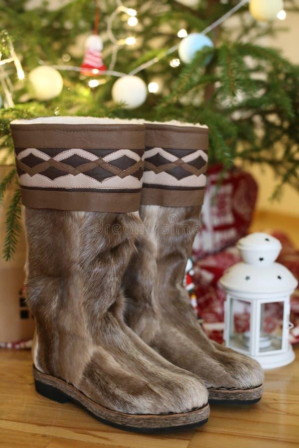 Un par de primer de las botas calientes en lanas se coloca cerca del árbol de navidad con los presentes en casa en un piso de mad foto de archivo