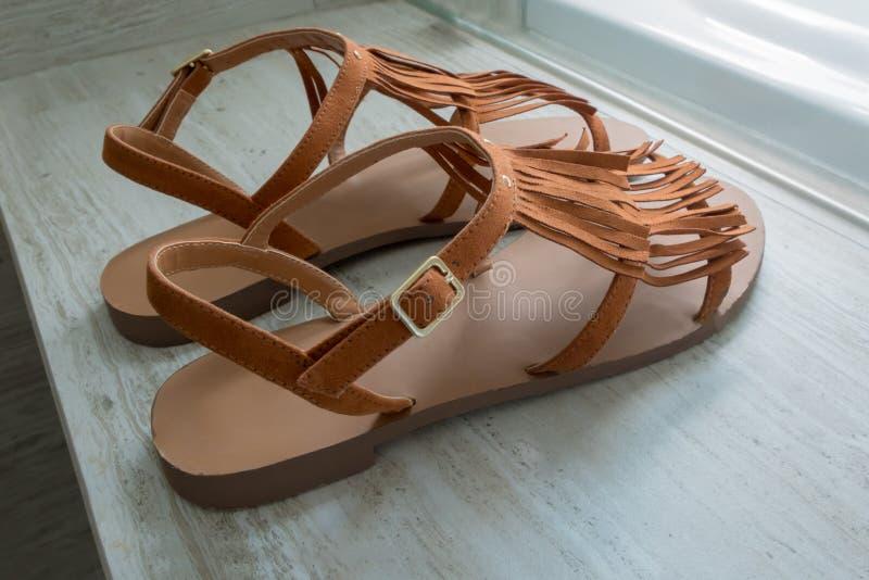 Un par de sandalias de cuero marrones modernas en el fondo de mármol imagen de archivo