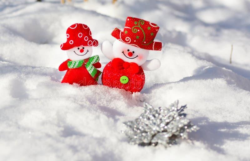 Un par de sonrisa suave se agrava muchacha y muchacho en el fondo blanco de la nieve Muñecos de nieve marido y esposa felices uno imagen de archivo