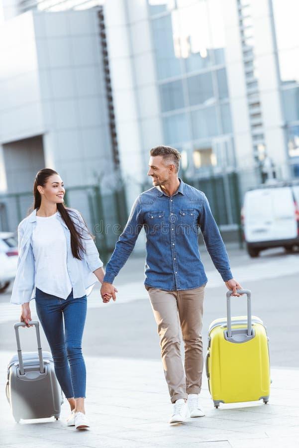 Un par de turistas que llevan a cabo las manos, tirando de su equipaje, mirando uno a y sonriendo en el fondo fotos de archivo libres de regalías