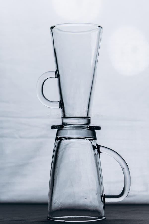 Un par de vidrios de cristal transparentes vac?os en un primer de plata gris del fondo dos tazas altas con una manija y una piern fotografía de archivo libre de regalías