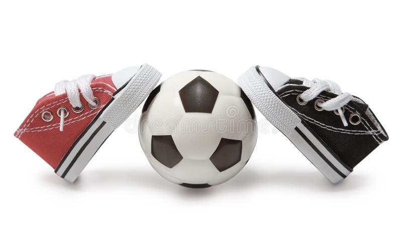 Un par de zapatillas de deporte de diversos colores se está inclinando en un balón de fútbol imagenes de archivo